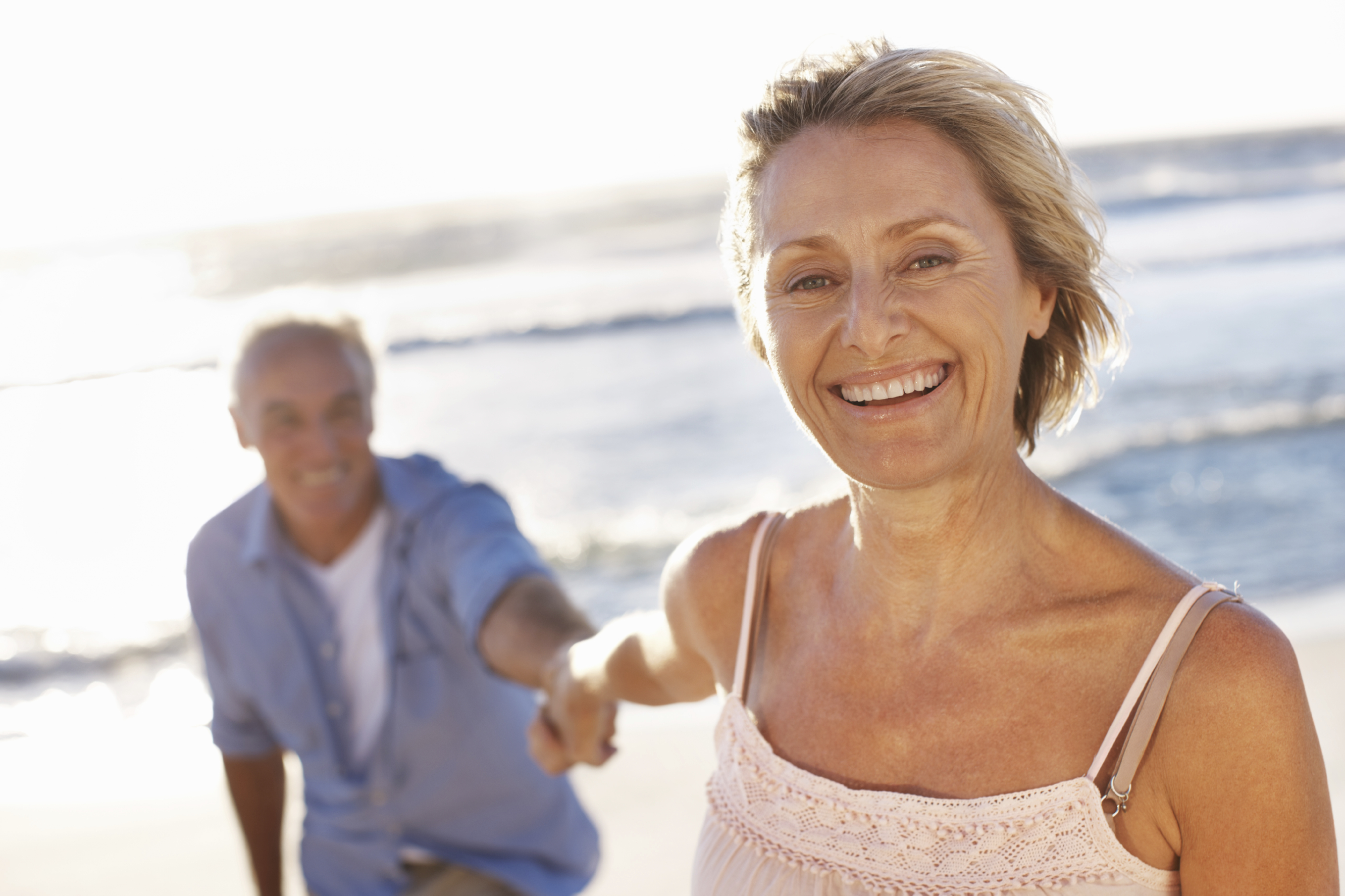 Older woman smiling at camera holding hands with man on a beach
