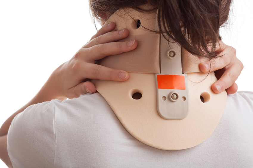 View of woman wearing neckbrace and holding it